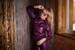 Modelo de moda en gafas de sol, chaqueta de cuero púrpura, pantalones de cuero que presentan con la mano en bolsillo cerca de la  imágenes de archivo libres de regalías