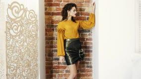 Modelo de moda en la blusa y la falda que presentan para la sesión fotográfica en el estudio en el fondo de la pared de ladrillo metrajes