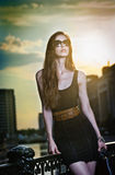 Modelo de moda en la calle con las gafas de sol y el vestido negro corto Foto de archivo