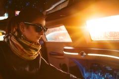 Modelo de moda en la chaqueta de cuero y las gafas de sol que se sientan en cenagoso imagen de archivo libre de regalías
