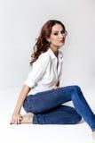 Modelo de moda en una blusa y vaqueros descalzo Fotos de archivo libres de regalías