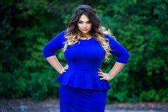 Modelo de moda enojado del tamaño extra grande en vestido azul al aire libre, mujer de la belleza con maquillaje profesional y pe Fotografía de archivo
