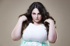 Modelo de moda enojado del tamaño extra grande, mujer gorda en fondo beige, cuerpo femenino gordo Foto de archivo libre de regalías