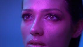 Modelo de moda fabuloso con sombreadores de ojos del brillo en relojes púrpuras de las luces de neón hacia arriba soñador metrajes