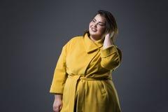 Modelo de moda feliz del tamaño extra grande en la capa amarilla y el sombrero negro, mujer gorda en fondo gris, cuerpo femenino  Foto de archivo libre de regalías