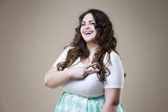 Modelo de moda feliz del tamaño extra grande en ropa casual, mujer gorda en fondo beige, cuerpo femenino gordo Foto de archivo libre de regalías