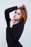 Modelo de moda femenino hermoso que presenta en vestido negro Imágenes de archivo libres de regalías