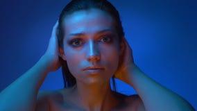Modelo de moda futurista brillante en las luces de neón azules frías que frotan ligeramente su cara y pelo que miran lentamente almacen de video