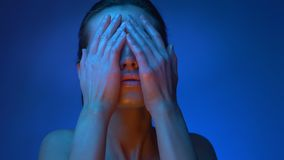 Modelo de moda futurista brillante en las luces de neón azules frías que ocultan su cara con las manos en fondo azul metrajes