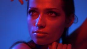 Modelo de moda futurista en luces de neón rojas y azules y echar un vistazo hacia arriba pensativamente y en cámara almacen de metraje de vídeo