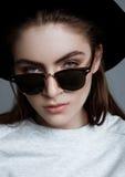 Modelo de moda hermoso con los vidrios y el sombrero negro Imagen de archivo libre de regalías