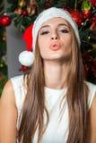 Modelo de moda hermoso divertido joven con los ojos oscuros, el pelo marrón y el sombrero de santa celebrando Año Nuevo en casa d Fotos de archivo