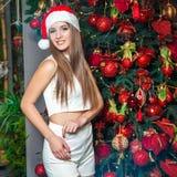 Modelo de moda hermoso divertido joven con los ojos oscuros, el pelo marrón y el sombrero de santa celebrando Año Nuevo en casa d Imagen de archivo libre de regalías