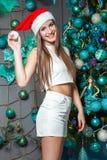 Modelo de moda hermoso divertido joven con los ojos oscuros, el pelo marrón y el sombrero de santa celebrando Año Nuevo en casa d Imagen de archivo