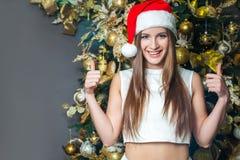 Modelo de moda hermoso divertido joven con los ojos oscuros, el pelo marrón y el sombrero de santa celebrando Año Nuevo en casa d Foto de archivo