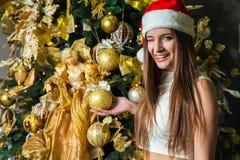 Modelo de moda hermoso divertido joven con los ojos oscuros, el pelo marrón y el sombrero de santa celebrando Año Nuevo en casa d Imagenes de archivo