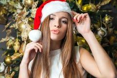 Modelo de moda hermoso divertido joven con los ojos oscuros, el pelo marrón y el sombrero de santa celebrando Año Nuevo en casa d Foto de archivo libre de regalías