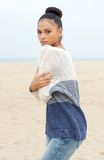 Modelo de moda hermoso en el suéter que se coloca en la playa solamente imagen de archivo