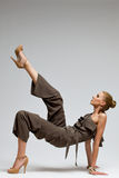 Modelo de moda hermoso en los tacones altos que golpean el aire con el pie. Foto de archivo