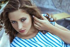 Modelo de moda hermoso joven que presenta en el barco Imagen de archivo