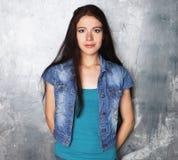 Modelo de moda joven que presenta en el estudio, fondo gris imagen de archivo
