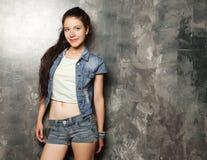 Modelo de moda joven que presenta en el estudio, fondo gris imagen de archivo libre de regalías