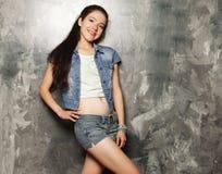 Modelo de moda joven que presenta en el estudio, fondo gris imágenes de archivo libres de regalías