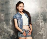 Modelo de moda joven que presenta en el estudio, fondo gris fotos de archivo