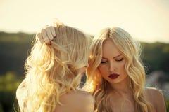 Modelo de moda de la belleza Girl Mirada de la manera Hermana a mujeres con los labios rojos en el fondo del cielo azul, familia fotos de archivo