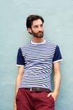 Modelo de moda masculino que se inclina contra la pared con la camisa rayada Imagen de archivo