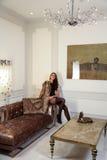 Modelo de moda moreno de fascinación que presenta en un sofá Foto de archivo libre de regalías