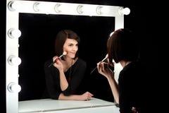 Modelo de moda que aplica maquillaje en espejo del vestuario Imagen de archivo