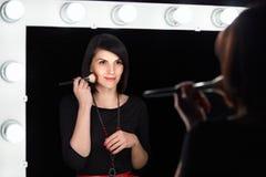 Modelo de moda que aplica maquillaje en espejo del vestuario Fotos de archivo libres de regalías