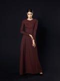 Modelo de moda que lleva el vestido marrón largo en fondo negro Imagenes de archivo