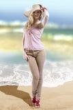 Modelo de moda que lleva la ropa del verano y el sombrero de paja elegantes en la playa imagenes de archivo