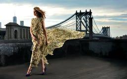 Modelo de moda que presenta el vestido de noche largo atractivo, que lleva en la ubicación del tejado Imágenes de archivo libres de regalías