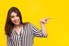 Modelo de moda que señala lejos en amarillo Fotografía de archivo libre de regalías