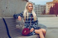 Modelo de moda rubio joven precioso que presenta al aire libre y que mira el aw Imagen de archivo libre de regalías