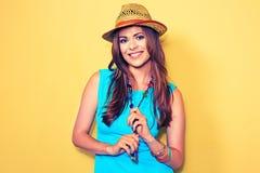 Modelo de moda sonriente que presenta contra fondo amarillo Fotos de archivo libres de regalías
