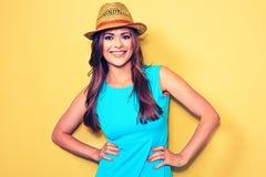 Modelo de moda sonriente que presenta contra fondo amarillo Foto de archivo
