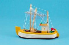 Modelo de nave hecho a mano de madera del barco en fondo azul Foto de archivo
