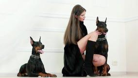 Modelo de pelo largo que lleva las botas negras largas del abrigo de pieles y de los tacones altos que tocan el doberman y que se almacen de metraje de vídeo