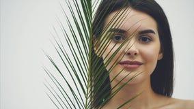 Modelo de sorriso bonito novo com composição natural, as pestanas longas e a folha verde das samambaias Termas, cuidados com a pe vídeos de arquivo