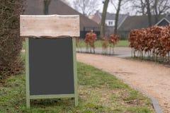 Modelo de um sinal do quadro com alguma madeira na parte superior fotografia de stock