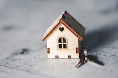 Modelo de una casa de madera con una cerradura y llaves en un fondo gris Concepto de la hipoteca Foco selectivo fotos de archivo libres de regalías