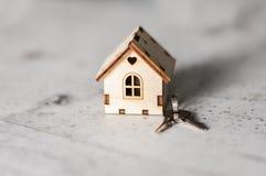 Modelo de una casa de madera con una cerradura y llaves en un fondo gris Concepto de la hipoteca Foco selectivo foto de archivo libre de regalías