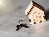 Modelo de una casa de madera con una cerradura y llaves en un fondo gris Concepto de la hipoteca Foco selectivo imagen de archivo libre de regalías