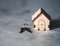 Modelo de una casa de madera con una cerradura y llaves en un fondo gris Concepto de la hipoteca Foco selectivo foto de archivo