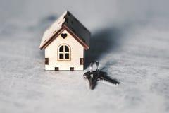 Modelo de una casa de madera con una cerradura y llaves en un fondo gris Concepto de la hipoteca Foco selectivo fotos de archivo