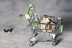 Modelo de una casa de madera con llaves de un cartand que hacen compras en un fondo gris Concepto de la hipoteca Foco selectivo imagenes de archivo